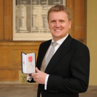 Aled with his MBE at Buckingham Palace.